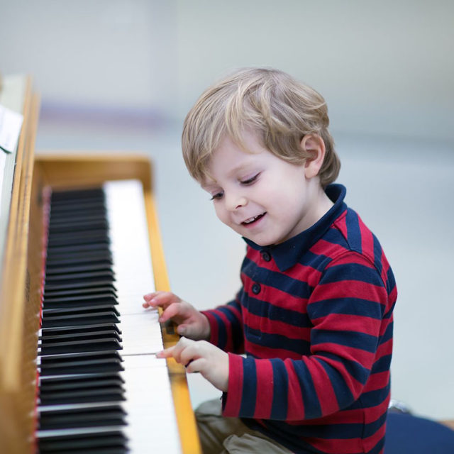 16660334 - two years old happy toddler boy playing piano